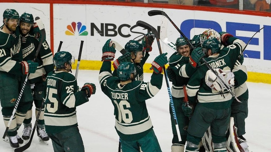Minnesota Wild left wing Zach Parise (11) and left wing Thomas Vanek (26) pile on goalie Devan Dubnyk, right, as they celebrate after defeating the St. Louis Blues 4-1 in Game 6 of an NHL hockey first-round playoff series in St. Paul, Minn., Sunday, April 26, 2015. (AP Photo/Ann Heisenfelt)