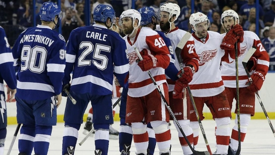 Tampa Bay Lightning center Vladislav Namestnikov (90), of Russia, and defenseman Matt Carle (25) shakes hands with Detroit Red Wings left wing Henrik Zetterberg (40), of Sweden, defenseman Kyle Quincey (27), center Pavel Datsyuk (13), of Russia, and left wing Drew Miller (20) shake hands after the Lightning defeated the Red Wings 2-0 during Game 7 of a first-round NHL Stanley Cup hockey playoff series Wednesday, April 29, 2015, in Tampa, Fla. (AP Photo/Chris O'Meara)
