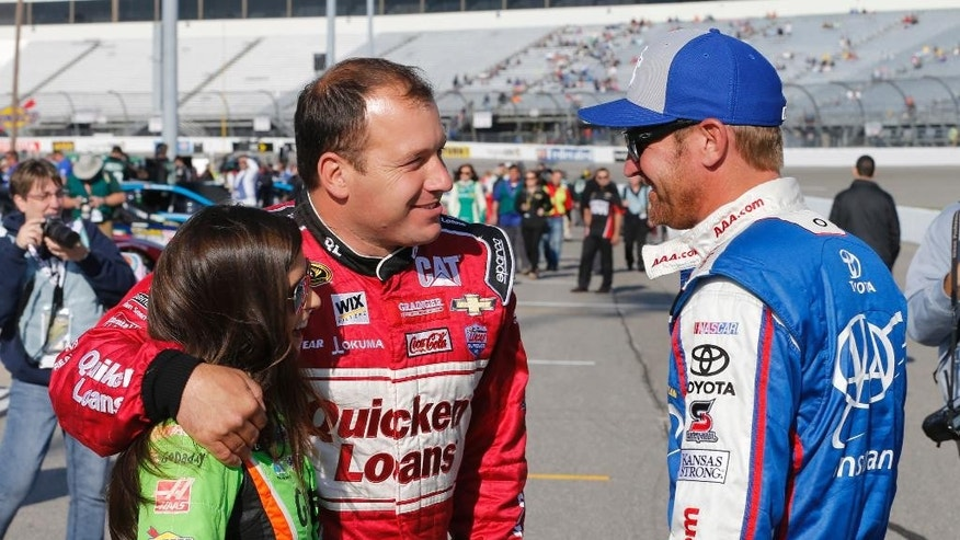 Ryan Newman, center, hugs Danica Patrick, left, as they talk to Clint Bowyer prior to qualifying for Saturday's Sprint Cup auto race at Richmond International Raceway in Richmond, Va., Friday, April 24, 2015. (AP Photo/Steve Helber)