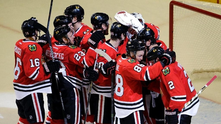 Chicago Blackhawks defenseman Duncan Keith, right, celebrates with teammates after they defeated the Nashville Predators 4-3 in Game 6 of an NHL Western Conference hockey playoff series Saturday, April 25, 2015, in Chicago. (AP Photo/Nam Y. Huh)