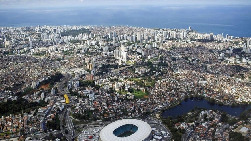 FILE - In this June 30, 2014 file photo, Arena Fonte Nova, bottom center, is seen in an aerial view of Salvador, Brazil. In April 2015, two World Cup stadiums were virtually put up for sale. Constructor OAS announced it was selling its stake in the Arena Fonte Nova and in the Arena das Dunas, in Natal.  (AP Photo/Rodrigo Abd, File)