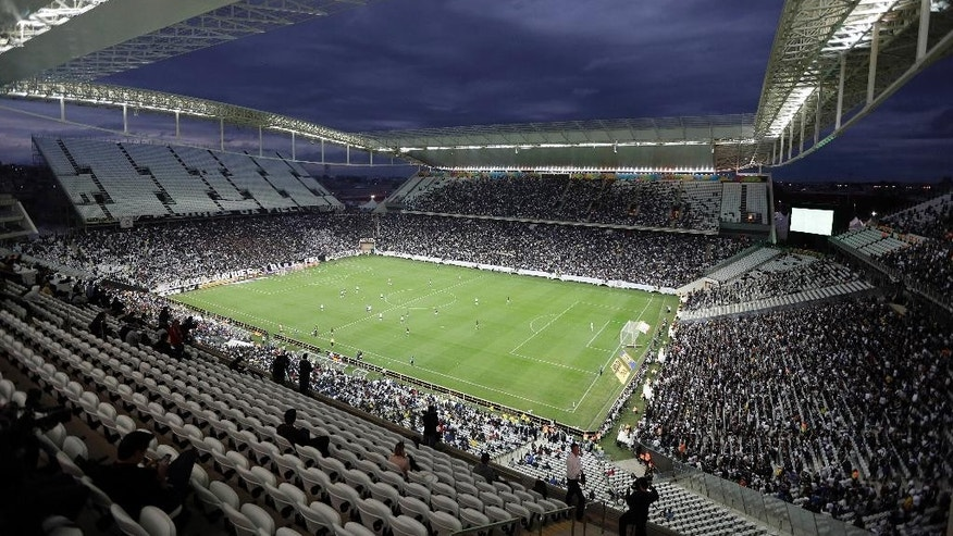 FILE - In this June 1, 2014 file photo, Corinthians and Botafogo players battle it out during a Brazilian soccer league match at the Itaquerao Stadium in Sao Paulo, Brazil. The stadium hosted the World Cup's opening match last June, a 3-1 win over Croatia for the host nation. But the venue wasn't fully finished at the time and only now it's been completed, 10 months after the tournament. A year after it handed over the stadium to FIFA for the World Cup, Corinthians still hasn't been able to reach a naming-rights deal for the arena. (AP Photo/Andre Penner, File)