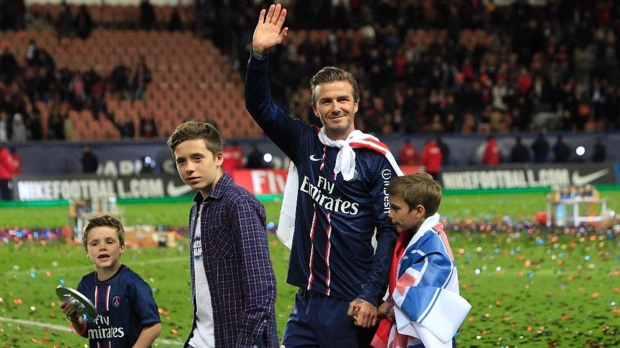 FILE - In this Saturday, May 18, 2013 file photo, Paris Saint-Germain's midfielder David Beckham, center, waves at supporters surrounded by his sons, Brooklyn, second from left, Cruz, left, and Romeo James, right, as he celebrates PSG's French League One title and his final match before retirement, at the Parc des Princes stadium, in Paris.  Beckham turns 40 on Saturday May 2, but since retiring, England's former captain continues to prosper off the field, where his multi-faceted life centers on celebrity and fashion, but also ambassadorial roles and an ambitious project to create a Miami team in the increasingly popular Major League Soccer. (AP Photo/Thibault Camus, file)