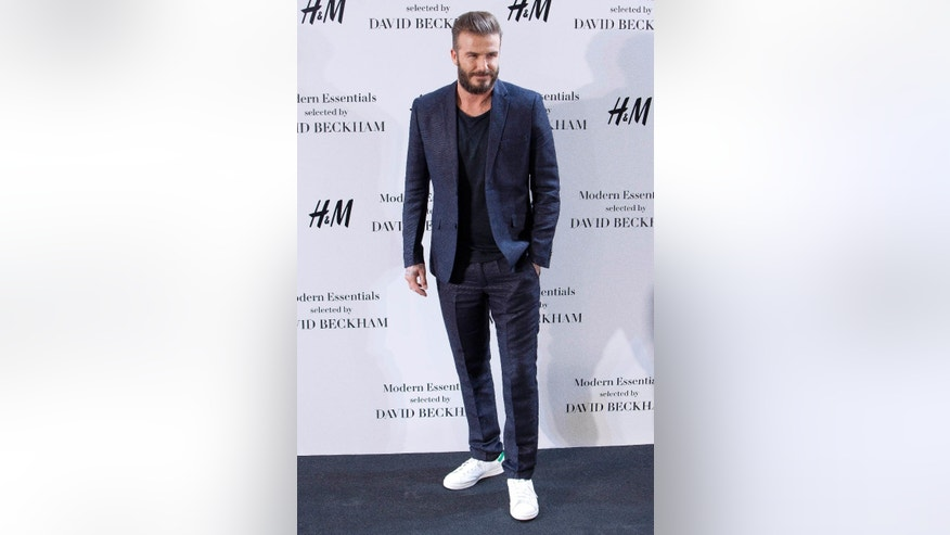 FILE - In this Friday, March 20, 2015 file photo, David Beckham poses for the photographers during a presentation of his collaboration with a fashion clothing brand, in Madrid.   Beckham turns 40 on Saturday May 2, but since retiring, England's former captain continues to prosper off the field, where his multi-faceted life centers on celebrity and fashion, but also ambassadorial roles and an ambitious project to create a Miami team in the increasingly popular Major League Soccer.  (AP Photo/Abraham Caro Marin, file)
