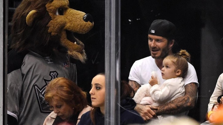 FILE - In this Saturday, April 12, 2014 file photo, David Beckham sits with his daughter, Harper, as Los Angeles Kings mascot Bailey visits while they watch the Kings play the Anaheim Ducks during the first period of an NHL hockey game, in Los Angeles.  Beckham turns 40 on Saturday May 2, but since retiring, England's former captain continues to prosper off the field, where his multi-faceted life centers on celebrity and fashion, but also ambassadorial roles and an ambitious project to create a Miami team in the increasingly popular Major League Soccer.   (AP Photo/Mark J. Terrill, file)