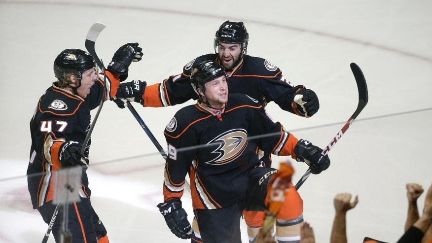 Anaheim Ducks' Hampus Lindholm,left, of Sweden, Matt Beleskey, center, and Kyle Palmieri, right, celebrate a goal by Beleskey against the Calgary Flames during the first period of Game 1 in the second round of the NHL Stanley Cup hockey playoffs, Thursday, April 30, 2015, in Anaheim, Calif. (AP Photo/Jae C. Hong)