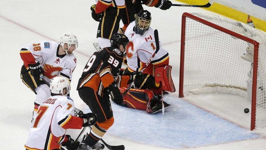 Anaheim Ducks' Matt Beleskey, center, watches his shot enter the net past Calgary Flames goalie Jonas Hiller, top, of Switzerland, during the first period of Game 1 in the second round of the NHL Stanley Cup hockey playoffs, Thursday, April 30, 2015, in Anaheim, Calif. (AP Photo/Jae C. Hong)