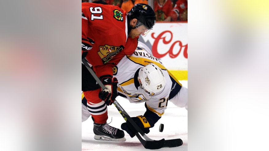 FILE- In this April 25, 2015, file photo, Chicago Blackhawks center Brad Richards, left, and Nashville Predators center Paul Gaustad battle for the puck during the second period in Game 6 of an NHL Western Conference hockey playoff series in Chicago. Richards was 13 for 19 on faceoffs in Game 6 against Nashville, helping Chicago advance to the conference semifinals for the third straight year. (AP Photo/Nam Y. Huh, File)