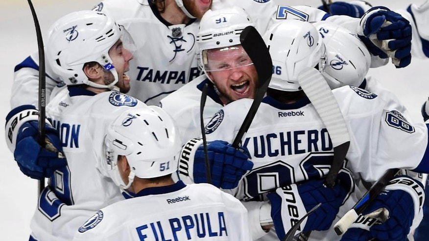 Tampa Bay Lightning right wing Nikita Kucherov (86) is hugged by Lightning center Steven Stamkos (91) as he celebrates with teammates after scoring the winning goal during the second overtime against the Montreal Canadiens of Game 1 of second-round playoff NHL hockey action Friday, May 1, 2015, in Montreal. (Ryan Remiorz/The Canadian Press via AP) MANDATORY CREDIT
