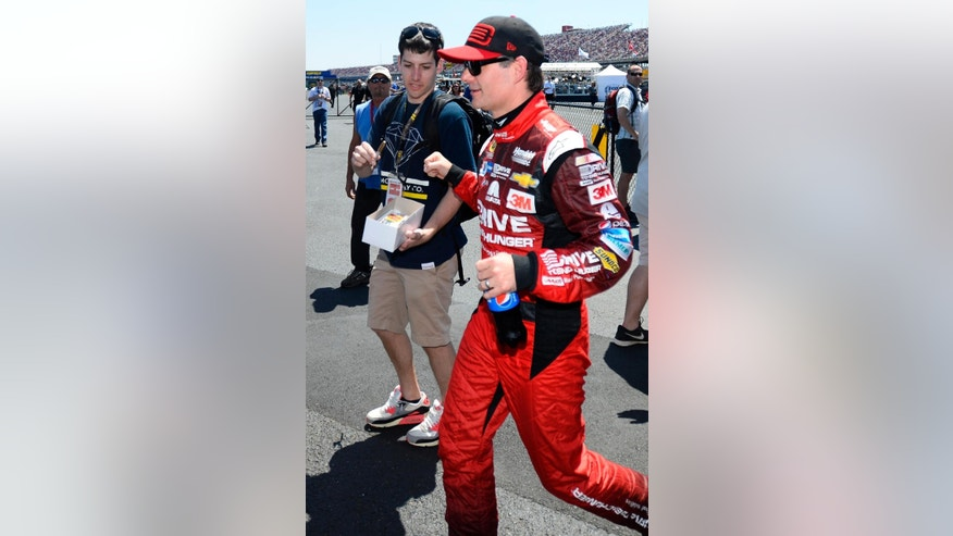 Pole winner Jeff Gordon, center, gets a fist-bump from a fan during qualifying for Sunday's NASCAR Sprint Cup Series auto race at Talladega Superspeedway, Saturday, May 2, 2015, in Talladega, Ala. (AP Photo/David Tulis)