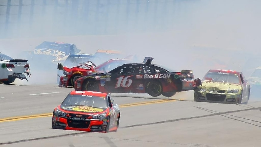 Greg Biffle (16) is lifted by Kevin Harvick, right, in a multi-car crash as Austin Dillon (3) drives past them during the Talladega 500 NASCAR Sprint Cup Series auto race at Talladega Superspeedway, Sunday, May 3, 2015, in Talladega, Ala. (AP Photo/Greg McWilliams)
