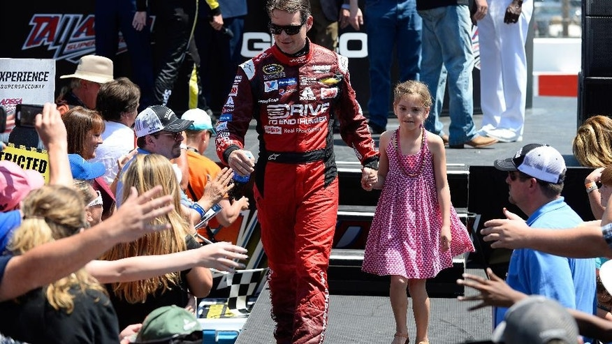 Pole winner Jeff Gordon, left, walks with his daughter Ella Sofia during introductions for the Talladega 500 NASCAR Sprint Cup Series auto race at Talladega Superspeedway, Sunday, May 3, 2015, in Talladega, Ala. (AP Photo/David Tulis)