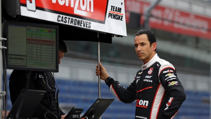 Helio Castroneves, of Brazil, watches practice from the pit area on the opening day at the Indianapolis Motor Speedway in Indianapolis, Sunday, May 3, 2015.  (AP Photo/Michael Conroy)