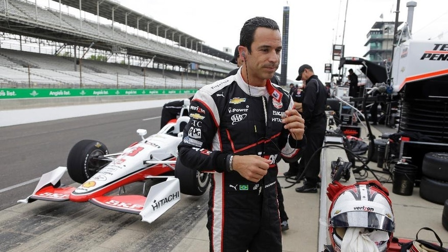 Helio Castroneves, of Brazil, walks away from his car after practicing on the opening day at the Indianapolis Motor Speedway in Indianapolis, Sunday, May 3, 2015.  (AP Photo/Michael Conroy)