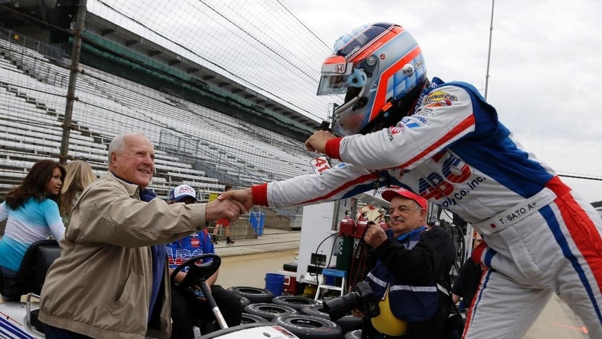 Takuma Sato, left, of Japan, greets car owner and four-time Indy 500 champion A.J. Foyt after Sato practiced on the opening day at the Indianapolis Motor Speedway in Indianapolis, Sunday, May 3, 2015.  (AP Photo/Michael Conroy)