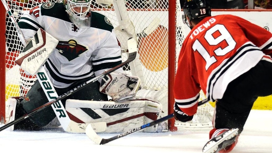 Minnesota Wild goalie Devan Dubnyk, left, fails to stop a shot and goal  by Chicago Blackhawks center Jonathan Toews, right, during the second period  of Game 2 in the second round of the NHL Stanley Cup hockey playoffs in Chicago, Sunday, May 3, 2015. (AP Photo/Nam Y. Huh)