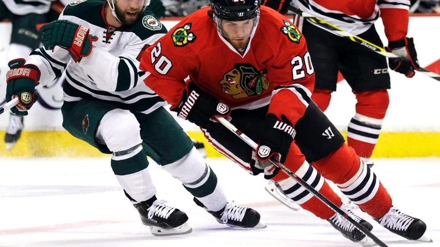 Chicago Blackhawks left wing Brandon Saad (20) controls the puck past Minnesota Wild left wing Jason Zucker (16) during the first period  of Game 2 in the second round of the NHL Stanley Cup hockey playoffs in Chicago, Sunday, May 3, 2015. (AP Photo/Nam Y. Huh)