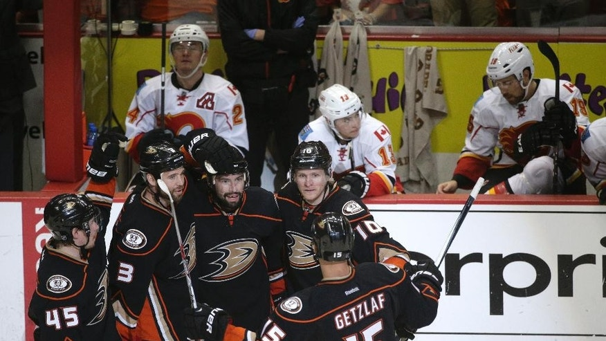 Anaheim Ducks' Sami Vatanen, from left, of Finland, Clayton Stoner, Nate Thompson, Corey Perry and Ryan Getzlaf celebrate a goal by Thompson in front of the Calgary Flames bench during the third period of Game 2 in the second round of the NHL Stanley Cup hockey playoffs, Sunday, May 3, 2015, in Anaheim, Calif. The Ducks won 3-0. (AP Photo/Jae C. Hong)