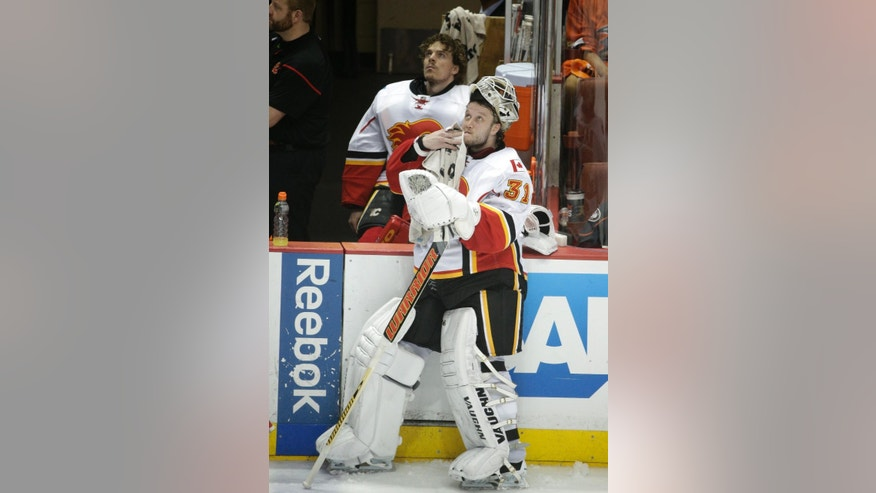 Calgary Flames goalies Karri Ramo, front, of Finland, and goalie Jonas Hiller, of Switzerland, watch a replay during the third period of Game 2 in the second round of the NHL Stanley Cup hockey playoffs against the Anaheim Ducks, Sunday, May 3, 2015, in Anaheim, Calif. The Ducks won 3-0. (AP Photo/Jae C. Hong)