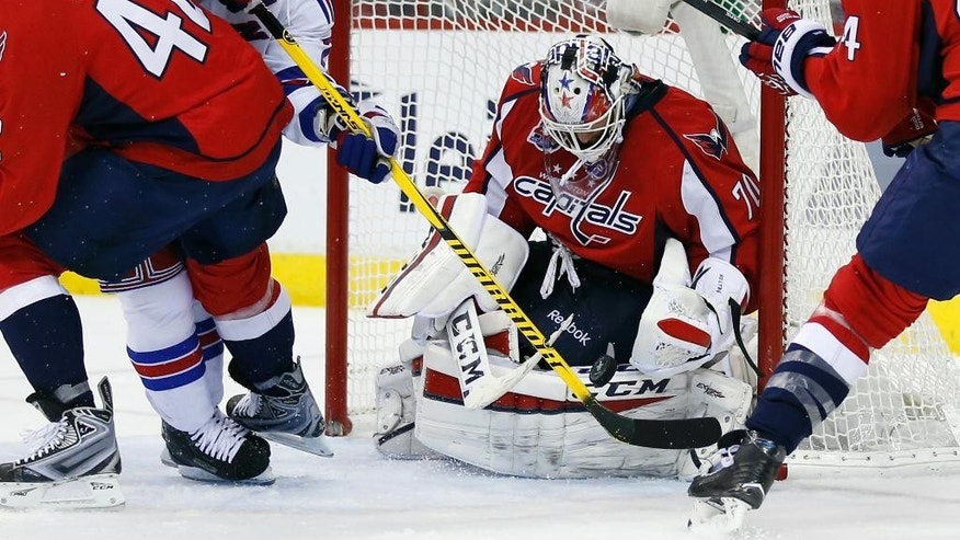 New York Rangers right wing Martin St. Louis (26) reaches over Washington Capitals right wing Joel Ward (42) as goalie Braden Holtby (70) blocks the shot during the second period of Game 3 in the second round of the NHL Stanley Cup hockey playoffs, Monday, May 4, 2015, in Washington. (AP Photo/Alex Brandon)