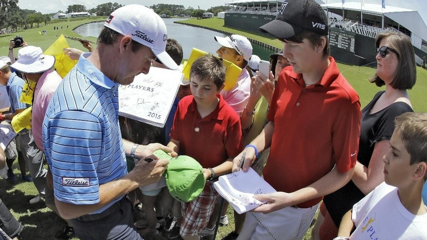 Jimmy Walker, left, signs autographs for fans as he comes off the 18th green during a practice round for The Players Championship golf tournament Tuesday, May 5, 2015, in Ponte Vedra Beach, Fla. (AP Photo/Chris O'Meara)