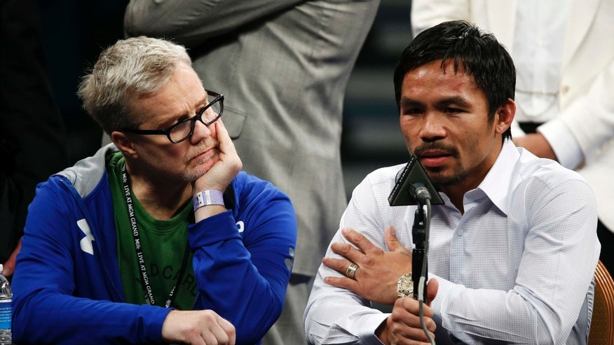 FILE - In this May 2, 2015 photo, trainer Freddie Roach, left, listens as Manny Pacquiao answers questions during a press conference following his welterweight title fight against Floyd Mayweather Jr. in Las Vegas. Pacquiao could face disciplinary action from Nevada boxing officials for failing to disclose a shoulder injury before the fight. Nevada Athletic Commission Chairman Francisco Aguilar said that the state attorney generalâs office will look at why Pacquiao checked ânoâ a day before the fight on a commission questionnaire asking if he had a shoulder injury. (AP Photo/John Locher)