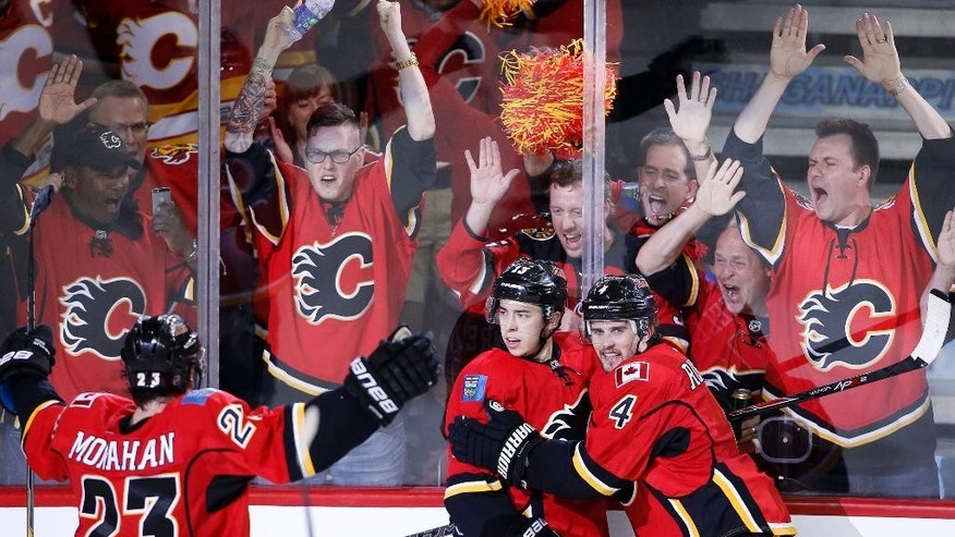 Calgary Flames' Johnny Gaudreau (13) celebrates his goal against the Anaheim Ducks with Sean Monahan (23) and Kris Russell (4) during the third period of Game 3 in the second round of the NHL Stanley Cup hockey playoffs, Tuesday, May 5, 2015, in Calgary, Alberta. (AP Photo/The Canadian Press, Larry MacDougal)