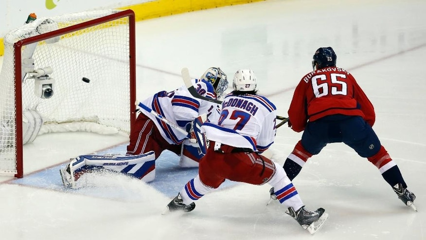 Washington Capitals left wing Andre Burakovsky (65), from Austria, scores the game winning goal past New York Rangers goalie Henrik Lundqvist, from Sweden, with defenseman Ryan McDonagh (27) nearby during the third period of Game 4 in the second round of the NHL Stanley Cup hockey playoffs, Wednesday, May 6, 2015, in Washington.  The Capitals won 2-1. (AP Photo/Alex Brandon)