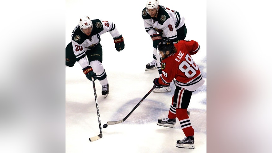 Chicago Blackhawks right wing Patrick Kane (88) shoots against Minnesota Wild defenseman Ryan Suter (20) and center Mikko Koivu (9) during the third period  of Game 2 in the second round of the NHL Stanley Cup hockey playoffs in Chicago, Sunday, May 3, 2015. The Blackhawks won 4-1. (AP Photo/Nam Y. Huh)