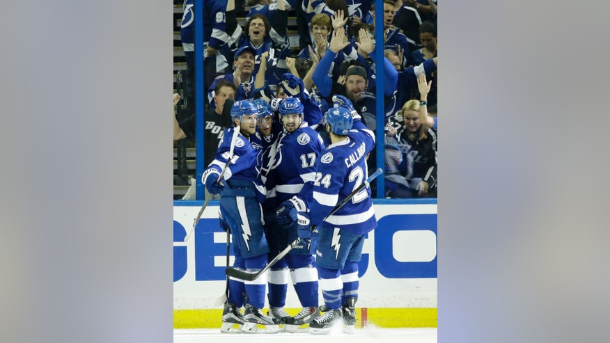 Teammates mob Tampa Bay Lightning center Alex Killorn (17) after he scored a goal during first period of Game 3 NHL second round playoff hockey action against the Montreal Canadiens, Wednesday, May 6, 2015, in Tampa, Fla. (AP Photo/Wilfredo Lee)