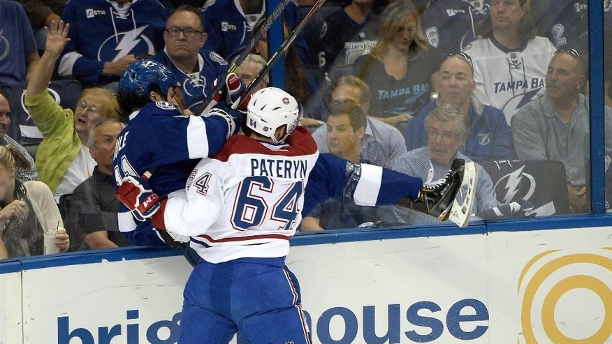 Tampa Bay Lightning center Brian Boyle (11) is slammed into the glass by Montreal Canadiens defenseman Greg Pateryn (64) during the first period of Game 3 of a second-round NHL Stanley Cup hockey playoff series in Tampa, Fla., Wednesday, May 6, 2015.(AP Photo/Phelan M. Ebenhack)
