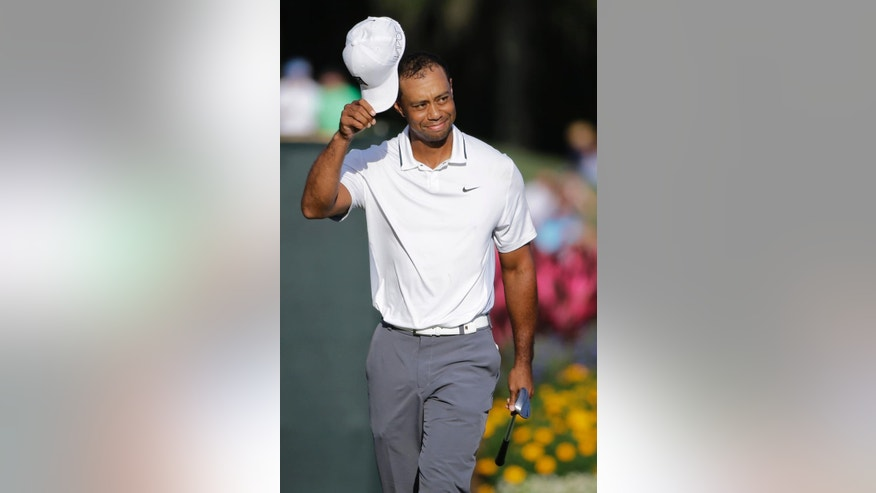 Tiger Woods removes his cap after making a birdie putt on the 17th hole during the first round of The Players Championship golf tournament Thursday, May 7, 2015, in Ponte Vedra Beach, Fla., Fla. (AP Photo/Chris O'Meara)