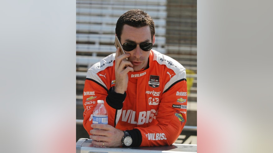 Simon Pagenaud, of France, makes a phone call before practice for the Grand Prix of Indianapolis auto race at the Indianapolis Motor Speedway in Indianapolis, Thursday, May 7, 2015. (AP Photo/Darron Cummings)