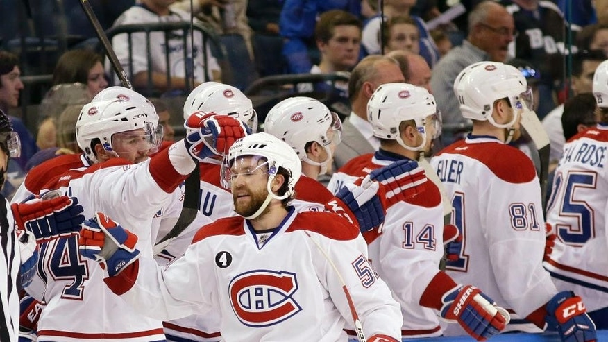 Montreal Canadiens center David Desharnais, foreground, is congratulated by teammates after he scored a goal during second period of Game 4 NHL second round playoff hockey action against the Tampa Bay Lightning, Thursday, May 7, 2015, in Tampa, Fla. (AP Photo/Wilfredo Lee)