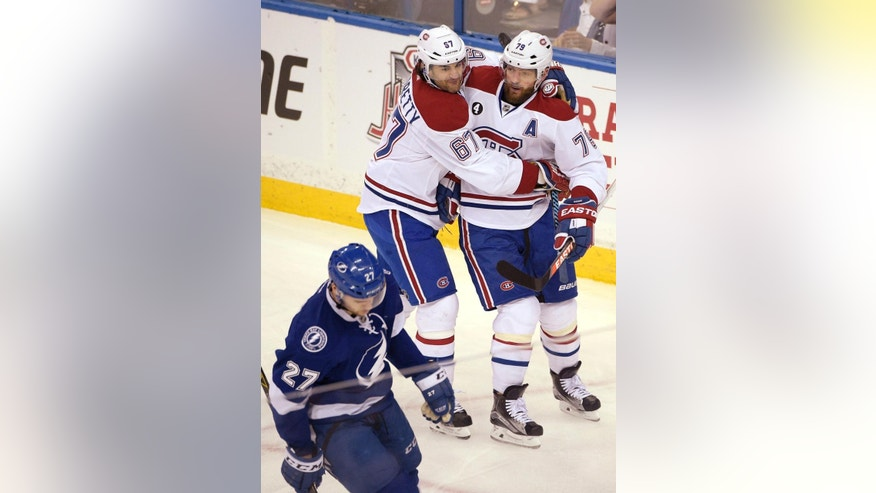 Montreal Canadiens defenseman Andrei Markov, right, is congratulated by left wing Max Pacioretty, center, after Markov scored, as Tampa Bay Lightning left wing Jonathan Drouin, left, skates away, during the first period of Game 4 of a second-round NHL Stanley Cup hockey playoff series in Tampa, Fla., Thursday, May 7, 2015. (AP Photo/Phelan M. Ebenhack)
