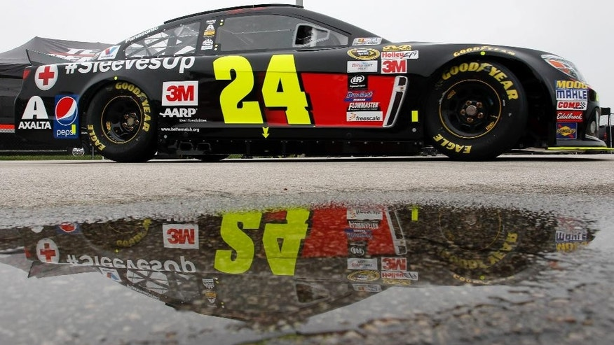 NASCAR driver Jeff Gordon (24) drives past standing rain water during practice for Saturday's Sprint Cup Series auto race at Kansas Speedway in Kansas City, Kan., Friday, May 8, 2015. (AP Photo/Colin E. Braley)
