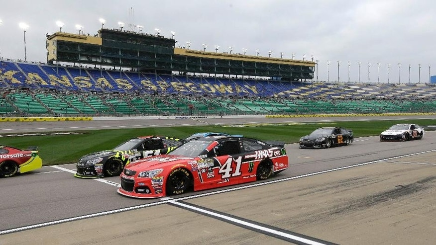 Competitors, including Kurt Busch (41), pull onto pit row during qualifying for Saturday's Sprint Cup Series auto race at Kansas Speedway in Kansas City, Kan., Friday, May 8, 2015. (AP Photo/Orlin Wagner)