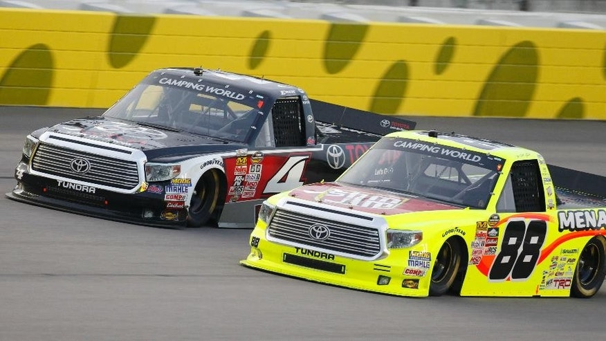 NASCAR drivers Erik Jones (4) and Matt Crafton (88) race side-by-side during a Truck Series auto race at Kansas Speedway in Kansas City, Kan., Friday, May 8, 2015. (AP Photo/Colin E. Braley)
