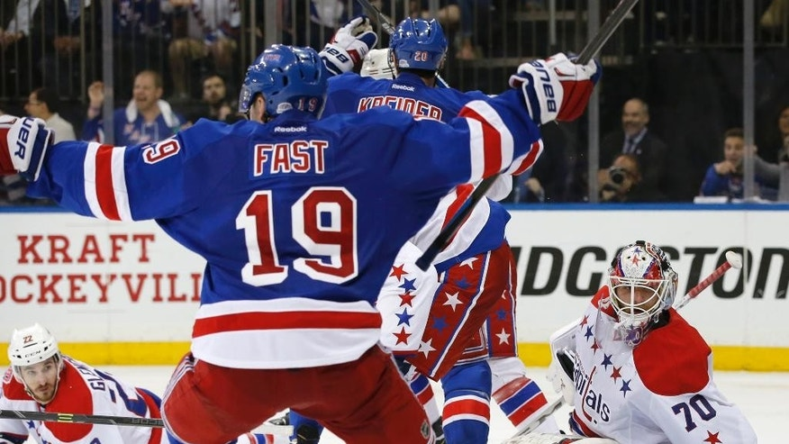 Washington Capitals left wing Curtis Glencross (22) and Washington Capitals goalie Braden Holtby (70) react as New York Rangers Jesper Fast (19) and other Rangers celebrate after the Rangers defeated the Capitals 2-1 in overtime of Game 5 in the second round of the NHL Stanley Cup hockey playoffs, Friday, May 8, 2015, in New York. The Rangers won 2-1. (AP Photo/Kathy Willens)