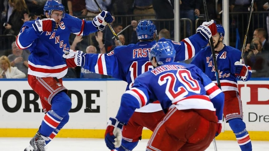 New York Rangers defenseman Ryan McDonagh, left, celebrates after scoring the winning goal in overtime during Game 5 in the second round of the NHL Stanley Cup hockey playoffs, Friday, May 8, 2015, in New York. The Rangers defeated the Capitals 2-1 to extend the series. (AP Photo/Kathy Willens)