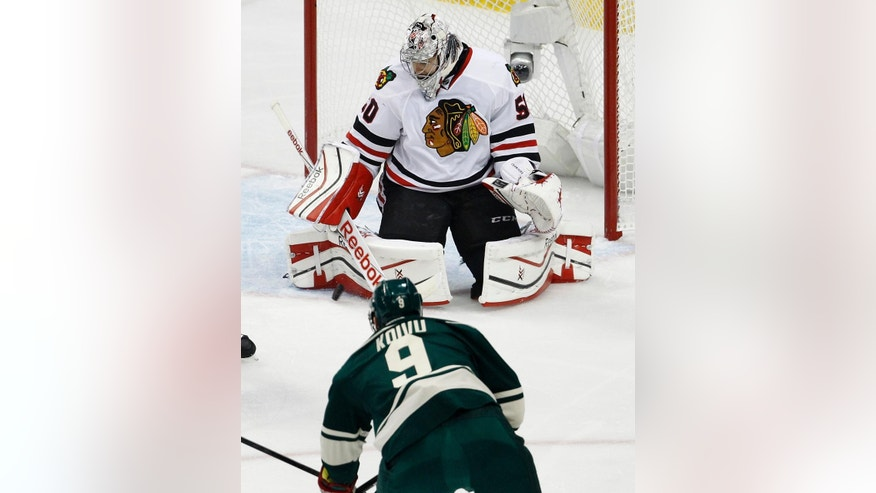 Chicago Blackhawks goalie Corey Crawford (50) swats away a shot by Minnesota Wild center Mikko Koivu (9), of Finland, during the first period of Game 4 in the second round of the NHL Stanley Cup hockey playoffs Thursday, May 7, 2015, in St. Paul, Minn. (AP Photo/Ann Heisenfelt)