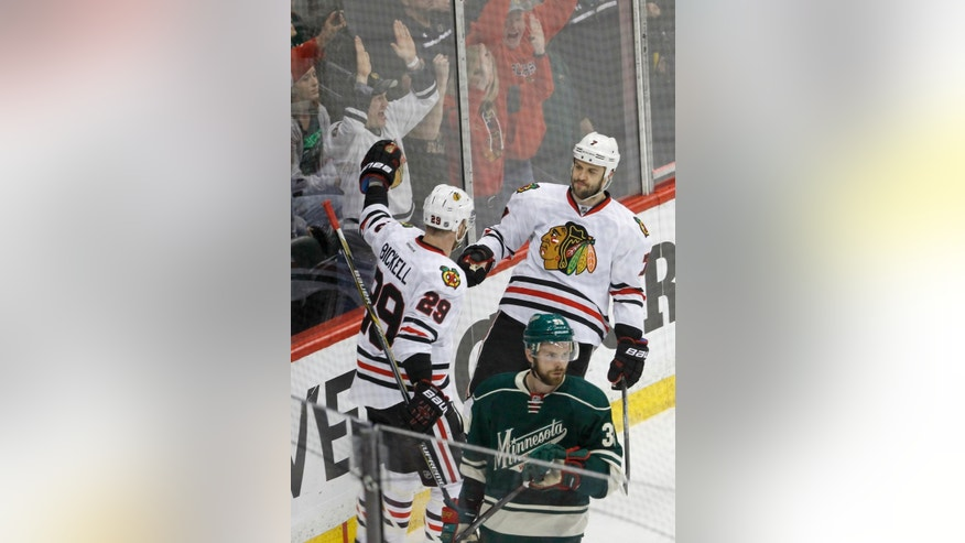 Chicago Blackhawks defenseman Brent Seabrook (7) and left wing Bryan Bickell (29) celebrate Seabrook's goal off Minnesota Wild goalie Devan Dubnyk as Wild defenseman Nate Prosser, front, looks away during the first period of Game 4 in the second round of the NHL Stanley Cup hockey playoffs Thursday, May 7, 2015, in St. Paul, Minn. (AP Photo/Ann Heisenfelt)