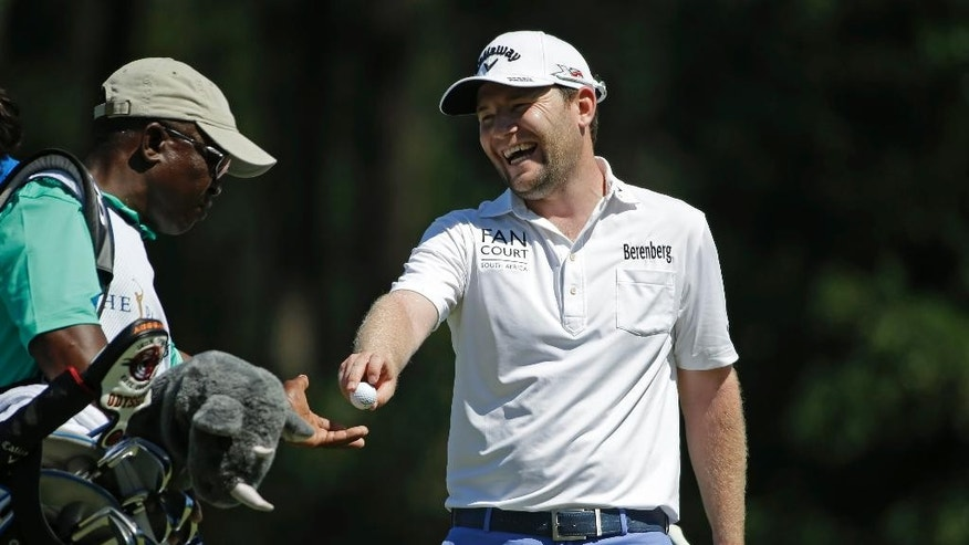 Branden Grace, of South Africa, hands his ball to caddie Zach Rasego, after making a birdie on the seventh hole during the second round of The Players Championship golf tournament Friday, May 8, 2015, in Ponte Vedra Beach, Fla. (AP Photo/Chris O'Meara)