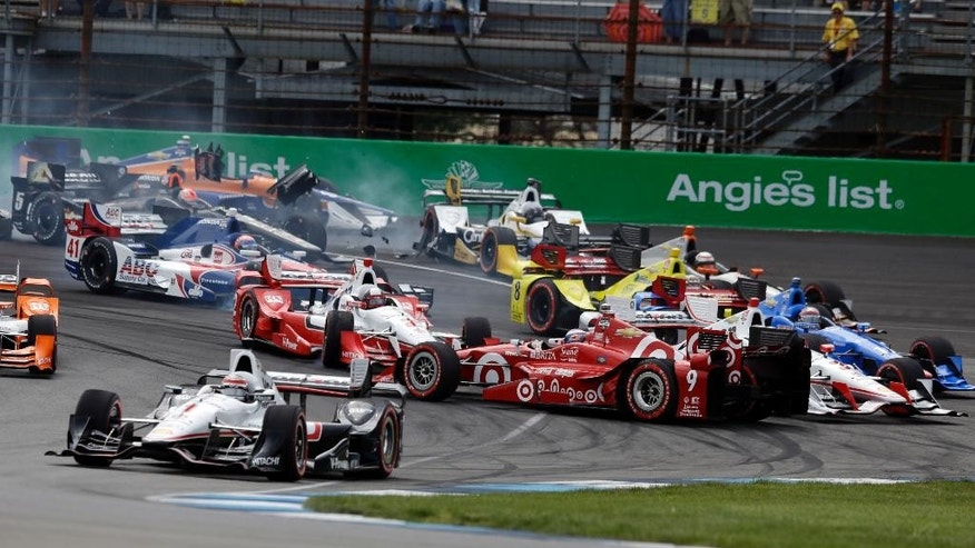 Will Power, of Australia, takes the lead as Scott Dixon, of New Zealand, spins on the start of the Grand Prix of Indianapolis auto race at Indianapolis Motor Speedway in Indianapolis, Saturday, May 9, 2015. (AP Photo/Michael Conroy)
