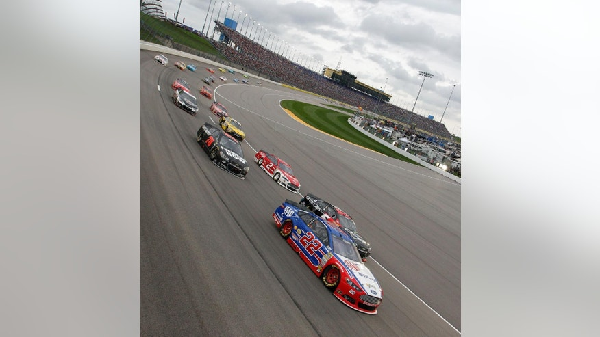 NASCAR driver Joey Logano (22) leads the first lap during a Sprint Cup Series auto race at Kansas Speedway in Kansas City, Kan., Saturday, May 9, 2015. (AP Photo/Colin E. Braley)