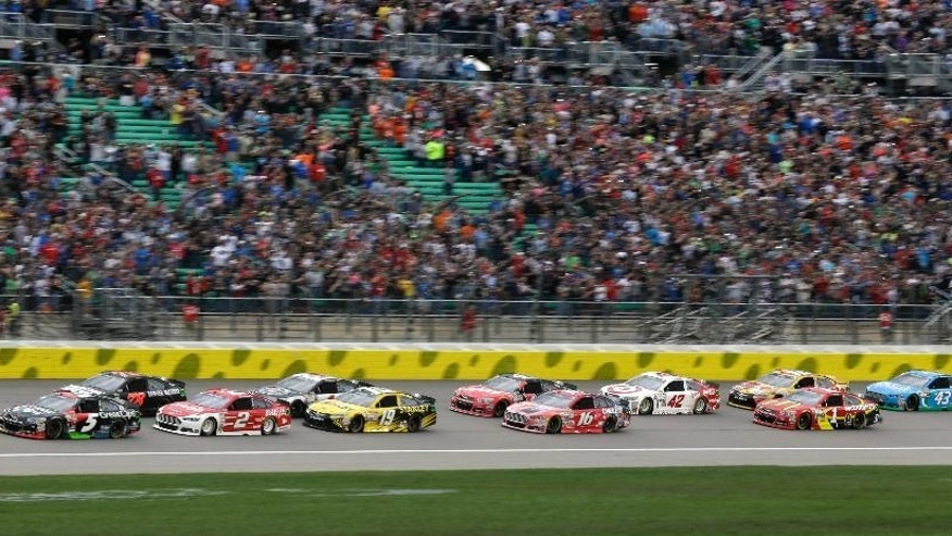NASCAR driver Joey Logano (22) leads the field into the first lap of a Sprint Cup Series auto race at Kansas Speedway in Kansas City, Kan., Saturday, May 9, 2015. (AP Photo/Orlin Wagner)