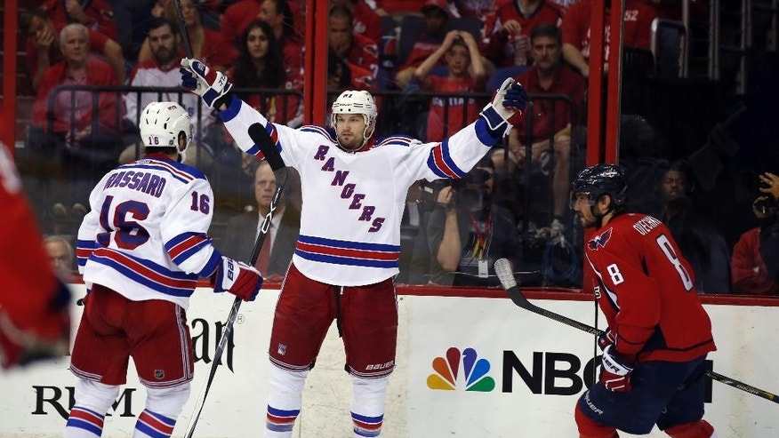 New York Rangers left wing Rick Nash (61) celebrates his goal with center Derick Brassard (16) with Washington Capitals left wing Alex Ovechkin (8), from Russia, nearby during the third period of Game 6 in the second round of the NHL Stanley Cup hockey playoffs, Sunday, May 10, 2015, in Washington. The Rangers won 4-3. (AP Photo/Alex Brandon)
