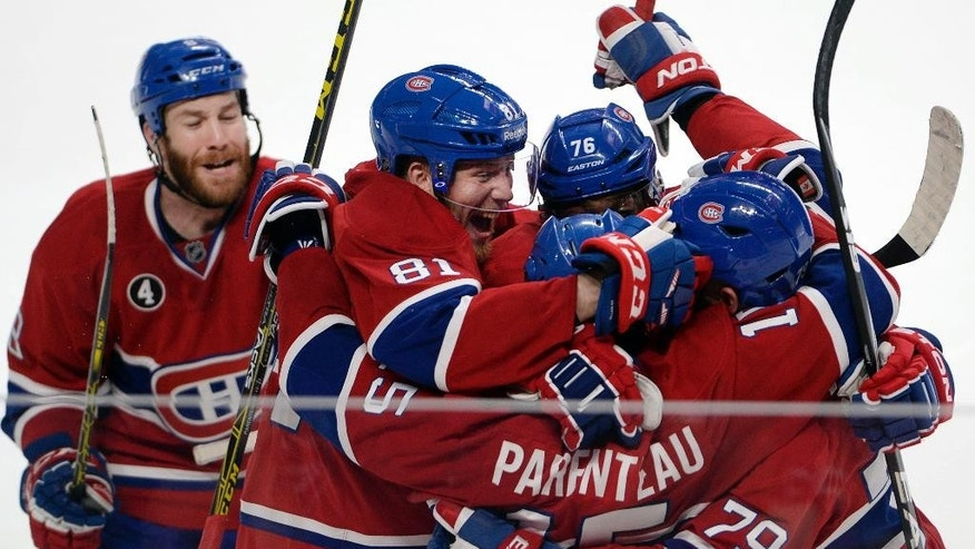 Montreal Canadiens right wing P.A. Parenteau (15) celebrates with teammates Andrei Markov (79), P.K. Subban (76), Lars Eller(81) and Brandon Prust, left, after scoring the winning goal against the Tampa Bay Lightning during the third period of Game 5 of a second-round NHL Stanley Cup hockey playoff series Saturday, May 9, 2015, in Montreal. (Ryan Remiorz/The Canadian Press via AP) MANDATORY CREDIT