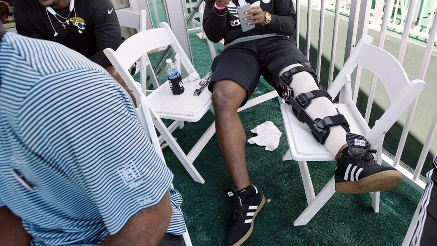 Jacksonville Jaguars first draft pick Dante Fowler Jr. sits with other team rookies in a tent overlooking the 17 green during the final round of The Players Championship golf tournament Sunday, May 10, 2015, in Ponte Vedra Beach, Fla. Fowler was hurt during rookie camp this week. (Bob Self/The Florida Times-Union via AP)