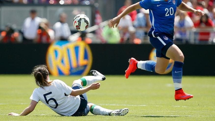 United States' Abby Wambach, right, jumps over a tackle by Ireland's Ciana Grant (5) during the second half of an exhibition soccer match Sunday, May 10, 2015, in San Jose, Calif. United States won 3-0. (AP Photo/Tony Avelar)